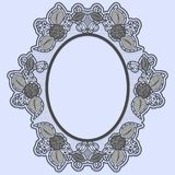 Oval lace frame on blue background. Black openwork with flowers. Royalty Free Stock Photos