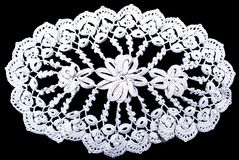 Oval lace tablecloth isolated on black background. White oval lace tablecloth isolated on black background. Cute out and texture for design. White pattern doily Stock Photography