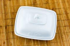 Oval maträtt för smör på en bambuservett arkivbilder
