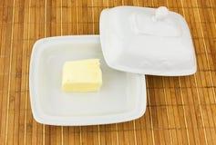 Oval maträtt med smör på bambuservett royaltyfri bild