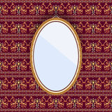 Oval mirror in a frame on the wall with patterned wallpaper. Royalty Free Stock Photos
