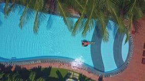 Oval pöl för hotell med hopfällbara stolar och kvinnan på vatten arkivfilmer