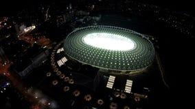 Oval-shaped φωτισμένο γήπεδο ποδοσφαίρου, εναέρια άποψη στην όμορφη πόλη νύχτας απόθεμα βίντεο
