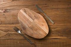 Oval skärbräda med kniven och gaffel på brun träbackgroun Arkivfoton