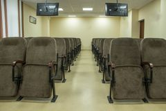 Large conference hall with chairs and monitors. Oval table made of natural wood with leather seats stock photos