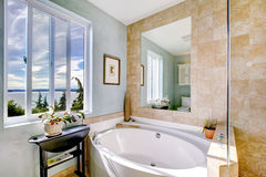 Oval tub with large mirror in luxury bathroom. Oval tub in luxury bathroom with mirror and windows Stock Photo