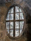 The oval window in the stone wall Stock Photo