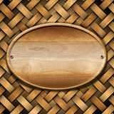 Oval Wood Board on Braided Wooden Background Royalty Free Stock Photo
