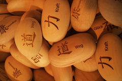 Oval wood pieces with japanese symbols. A pile of egg shaped wood pieces engraved with Japanese symbols and their meaning in German written next to them. For Stock Photography