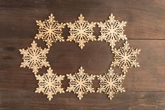 Oval snowflake frame design on wooden table. Oval wooden snowflake frame design on wooden table Royalty Free Stock Image