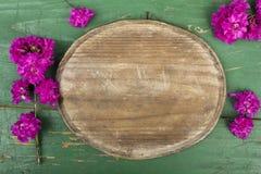 Ovala platta- och rosa färgblommor på retro träplankor Royaltyfria Bilder