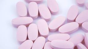 Ovale roze tabletten op plaat stock videobeelden
