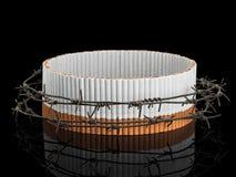 Ovaler Zigarettenschutz hinter einem Stacheldraht Stockfotos