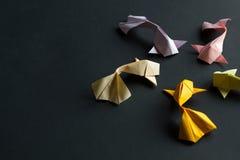 Ovalt ramdiagram av handgjorda fiskar f?r karp f?r koi f?r origami f?r pappers- hantverk guld- p? svart bakgrund Slapp fokus arkivbilder