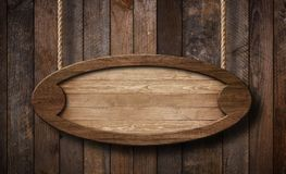 Ovalt trätecken som hänger på rep med träplankabakgrund fotografering för bildbyråer