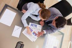 Ovanför beskåda av konsulenten som analyserar statistik med henne beställaren Royaltyfri Bild