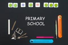 Ovanför brevpappertillförsel och textgrundskola för barn mellan 5 och 11 år på svart tavla royaltyfri bild