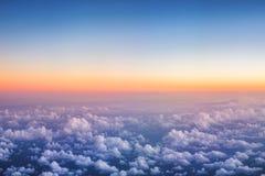 Ovanför de pösiga molnen på solnedgång Arkivbild