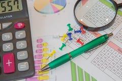 Ovanför lögner pennan, förstoringsapparaten och räknemaskinen Analysering av finansiella data på räknemaskinen Royaltyfri Fotografi