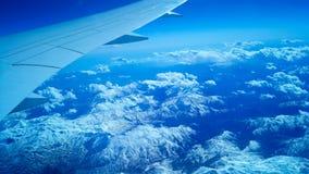 Ovanför landet eller berget och snön från flygplanet med vingen Arkivfoton