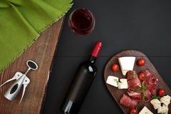 Ovanför lekmanna- stilleben för över huvudet siktslägenhet av olikt ost för sortiment och matvaruaffär och rött vin på ett gammal royaltyfria foton