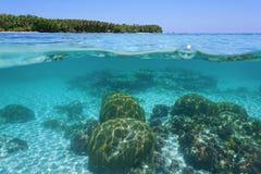 Ovanför och nedanför havsyttersida med koraller och ön arkivfoto