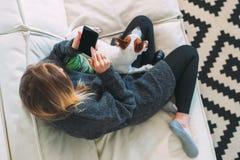 ovanför sikt Den unga kvinnan sitter på den vita soffan, genom att använda smartphonen Det finns den närliggande hunden arkivbilder