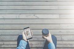 ovanför sikt Sikt från ögon Närbild av smartphonen med diagram, grafer, diagram, data på skärmen och koppen kaffe Arkivbild