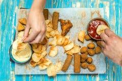 ovanför sikt händer tar mellanmål för öl, chiper, ost, smällare från ett träbräde fotografering för bildbyråer