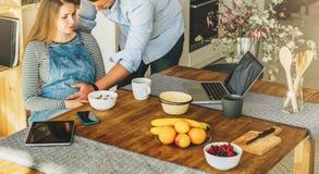 ovanför sikt Ungt gift par i kök Gravida kvinnan sitter på tabellen, man rymmer hennes gravida buk Royaltyfri Bild