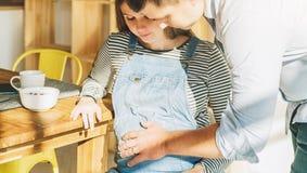 ovanför sikt Ungt gift par i kök Gravida kvinnan sitter på tabellen, man rymmer hennes gravida buk Royaltyfri Foto