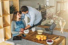 ovanför sikt Ungt gift par i kök Gravida kvinnan sitter på tabellen, man rymmer hennes gravida buk Royaltyfria Foton