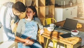 ovanför sikt Ungt gift par i kök Gravida kvinnan sitter på tabellen, man rymmer hennes gravida buk Arkivfoto