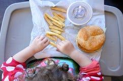 Ovanför sikten av lilla flickan som är klar att äta snabbmat fotografering för bildbyråer