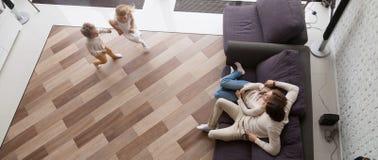 Ovanför siktsföräldrar som vilar på soffabarn som kör att spela tillsammans fotografering för bildbyråer