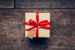 Ovanför den bruna gåvaasken och rött band med etiketten på wood bakgrund Royaltyfri Foto