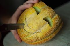 Ovanlig allhelgonaaftonmelon som klipper process, frö och rester på de köksbord-, kniv- och manhänderna Royaltyfri Foto