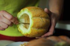 Ovanlig allhelgonaaftonmelon som klipper process, frö och rester på de köksbord-, kniv- och manhänderna Royaltyfria Bilder