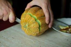 Ovanlig allhelgonaaftonmelon som klipper process, frö och rester på köksbordet Arkivbild