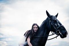 Ovanlig brud på bröllop på svart häst utomhus Fotografering för Bildbyråer