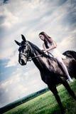 Ovanlig brud på bröllop på svart häst utomhus Royaltyfria Bilder