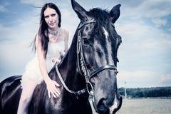 Ovanlig brud på bröllop på svart häst utomhus Royaltyfri Bild