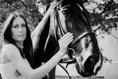 Ovanlig brud på bröllop på svart häst utomhus Royaltyfri Fotografi
