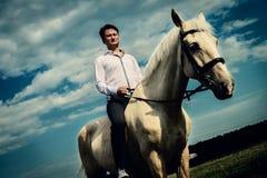 Ovanlig brudgum på bröllop på den vita hästen utomhus Royaltyfri Foto