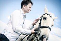 Ovanlig brudgum på bröllop på den vita hästen utomhus Arkivbilder
