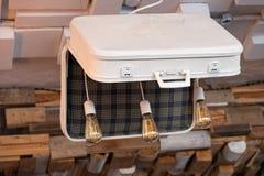 Ovanlig ljuskrona som göras från den gamla resväskan med tre Edison exponeringsglaslightbulbs inom Retro stil för vit resväska me royaltyfria foton