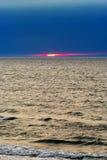 Ovanlig solnedgång på havet med solen som ses delvis till och med det tjocka lagret av mörka moln Arkivfoton