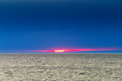 Ovanlig solnedgång på havet med solen som ses delvis till och med det tjocka lagret av mörka moln Royaltyfria Foton