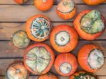 Ovanlig typ av pumpaturbansquash på en träräknare Många orange pumpa på en trätabell Pumpa för en ferie arkivbild