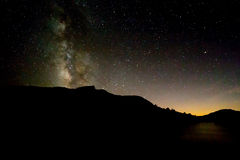 Ovannämnd svart kontur för Vintergatan av berget med beträffande solnedgångglöd Royaltyfri Foto
